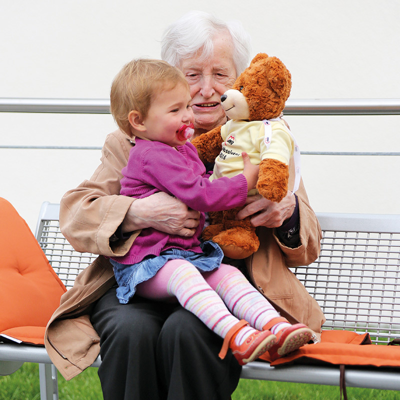 Seniorin, Kleinkind und Teddybär